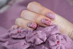 Rosa manikyr i samverkan med beståndsdelarna av kläder Arkivbild