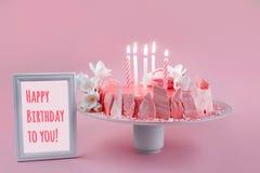 Rosa moussekaka med spegelglasyr som dekoreras med makron, blommor och ramen med text för lycklig födelsedag över rosa ferie royaltyfria foton