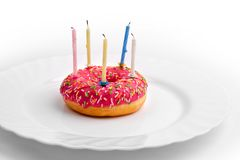 Rosa munk på den vita plattan som födelsedagkakan med stearinljus på vit bakgrund royaltyfri foto