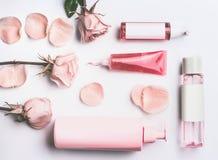 Rosa naturliga kosmetiska produkter med nödvändig olja för rosor: stelna, lotion-, serum- och färgpulverflaskor och rör för rosva Royaltyfri Foto