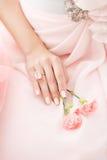 Rosa nejlikablomma i händerna av en flicka på en rosa bakgrund Arkivbilder