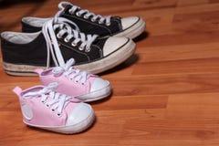 Rosa neugeborene Schuhe und Paare der erwachsenen Turnschuhe stockfotos