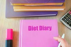 Rosa Notizbuch mit dem Aufschriftdiättagebuch, -taschenrechner und -hand mit einem Stift Nähren Sie Plangesunde ernährung, -c$näh lizenzfreie stockbilder