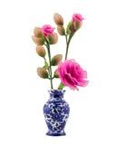 Rosa nylontygblomma i blå keramisk vas på isolatvitbakgrund Royaltyfria Foton