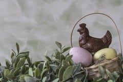 Rosa och gula påskägg i korg med sidor, med chokladhöna, royaltyfri foto