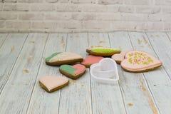Rosa och kulöra pepparkaka- och honungkakor och hjärta-formade kakor ligger i en smutsig hög på en ljus träbakgrund N?rliggande v royaltyfria foton