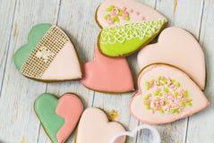 Rosa och kulöra pepparkaka- och honungkakor och hjärta-formade kakor ligger i en smutsig hög på en ljus träbakgrund N?rliggande v arkivfoton