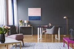 Rosa och marinblå målning i grå vardagsruminre med fl royaltyfri fotografi