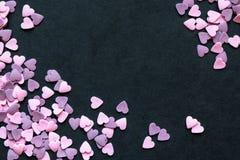 Rosa och purpurfärgade Sugar Heart Shape Decoration Background på svart yttersida med fritt utrymme Arkivfoto