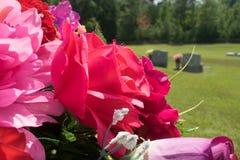 Rosa och rött tyg blommar i kyrkogård royaltyfri bild
