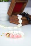 Rosa och vit pracelet i träask royaltyfri foto