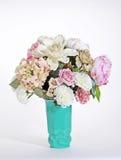 Rosa och vita blommor i en turkosgräsplanDeco vas Arkivfoton