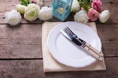 Rosa och vita blommor, stearinljus i blå lykta, kniv och gaffel Royaltyfri Bild