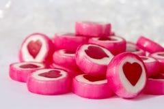 Rosa och vita candys med röda hjärtor på vit bakgrund fotografering för bildbyråer