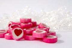 Rosa och vita candys med röda hjärtor på vit bakgrund arkivbilder