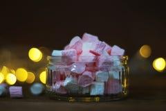 Rosa och vitt marshmellowsinexponeringsglas som isoleras över trätabell- och bokehljus på bakgrund Time för jul royaltyfri bild
