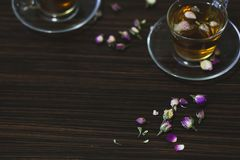 Rosa orientaliskt te i genomskinliga exponeringsglaskoppar på mörk träbakgrund arkivfoto