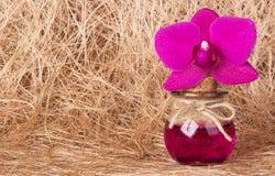 Rosa orkidé och flaska av elixir på bakgrunden av naturlig fiber alternativt magasin för brunnsort för medicin för objekt för gin Arkivfoto
