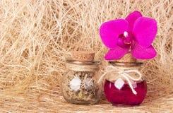 Rosa orkidé och två glasflaskor på sisalhampa för naturlig fiber Tvål-, handduk- och blommasnowdrops bottles cosmeticen Ekologisk Arkivbild