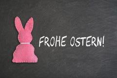 Rosa Osterhase mit Text 'Frohe Ostern 'auf einem Tafelhintergrund Transla stockbilder