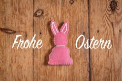 Rosa Osterhase mit Text 'Frohe Ostern 'und einem hölzernen Hintergrund Übersetzung: 'Fröhliche Ostern ' lizenzfreie stockbilder
