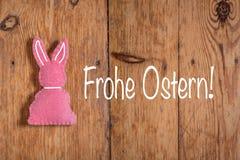 Rosa Osterhase mit Text 'Frohe Ostern 'und einem hölzernen Hintergrund Übersetzung: 'Fröhliche Ostern ' lizenzfreie stockfotografie