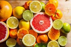 Rosa Pampelmuse und andere Zitrusfrucht gegen hölzernen Hintergrund Lizenzfreies Stockfoto