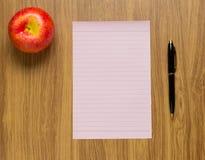 Rosa Papier auf dem Schreibtischhintergrund Lizenzfreie Stockfotos