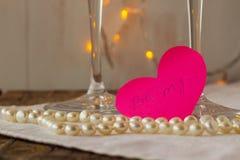 Rosa Papierherz mit Liebesgeständnis und -perlen Stockfoto