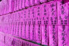 Rosa pappers- bönflaggor eller snedsteg med namn i kinesiskt svart färgpulver i den Thien Hau templet av Cho Lon, område 5, Saigo royaltyfria foton
