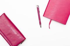 Rosa para mujer rosado del diario, de la pluma y de la cartera en un fondo blanco Imagen de archivo libre de regalías