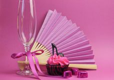 Rosa Parteidekorationen mit Fan, Champagnerglas und hohem Absatz beschuhen kleinen Kuchen Stockbilder