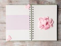 Rosa Pastellherzen und purpurrote Ringmappe der leeren Karte Stockbild