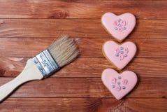 Rosa pepparkakakakahjärtor och borste arkivfoton