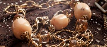 Rosa Perlen, goldene Kette auf brauner Spitze lizenzfreies stockfoto