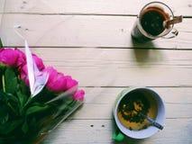rosa Pfingstrosenblumen, eine Tasse Tee und ein Tasse Kaffee auf weißen Brettern Lizenzfreie Stockfotos