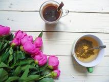 rosa Pfingstrosenblumen, eine Tasse Tee und ein Tasse Kaffee auf weißen Brettern Stockbilder