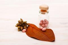Rosa Pillen mit orange Blatt auf Holztisch Lizenzfreie Stockfotografie