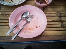 Rosa Plastikteller, Löffel und Gabelstahl sind die Tabelle, die mit Kopienraum hölzern ist Lizenzfreies Stockfoto
