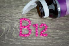 Rosa preventivpillerar som bildar form till alfabetet B12 på wood bakgrund Arkivfoton