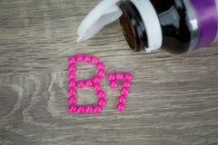 Rosa preventivpillerar som bildar form till alfabetet B7 på wood bakgrund Arkivfoto