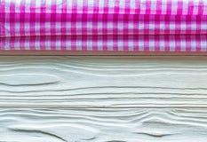 Rosa quadrierte Baumwolltischdecke auf hölzernem Brett Stockbilder
