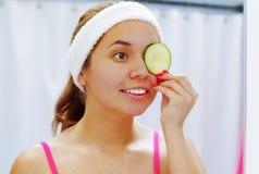 Rosa que lleva atractivo de la mujer joven superior y venda blanca, cubriendo un ojo con la rebanada de pepino usada para la piel Foto de archivo libre de regalías