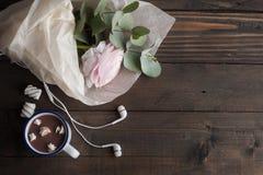 Rosa Ranunculus, Kopfhörer, heiße Schokolade stockfotografie