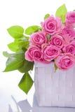 Rosa ro i en gåvakorg arkivfoto