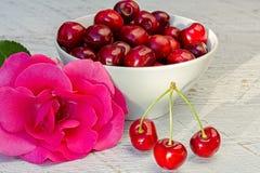 Rosa roja de la cereza dulce y del rosa en la tabla blanca Fotos de archivo libres de regalías