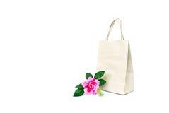 Rosa rosa färgblomma med den pappers- shoppingpåsen som isoleras på viten b arkivfoto