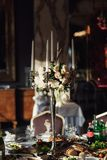 Rosa rosafarbene Blumenblätter ligh zwischen den weißen Kerzen, die auf dem dinn stehen lizenzfreies stockbild
