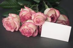 Rosa rosbukett med den tomma vita etiketten royaltyfri foto