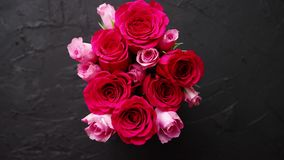 Rosa rosbukett som packas i röd ask och förläggas på svart stenbakgrund